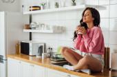Fotografie Krásná žena drží šálek kávy, zatímco sedí se zavřenýma očima na pracovní ploše kuchyně