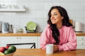 Selektivní zaměření krásné brunetky žena se usmívá a drží šálek kávy u stolu v kuchyni