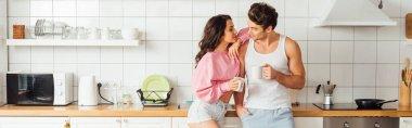 Mutfakta bir fincan kahveyle yakışıklı erkek arkadaşı kucaklayan panoramik genç bir kadın.