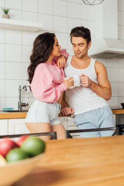 Selective focus of young couple with cups of coffee standing near worktop in kitchen stock vector