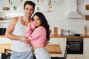 Handsome man smiling at camera while embracing attractive woman in kitchen stock vector