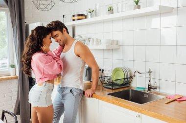 Beautiful sexy woman hugging smiling boyfriend in kitchen stock vector