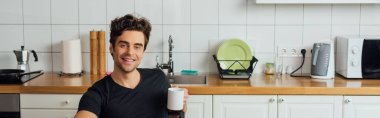 Panoramic shot of handsome man smiling at camera and holding cup of coffee in kitchen stock vector