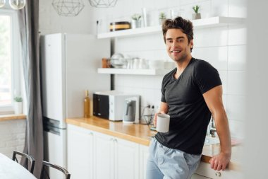 Selective focus of handsome man smiling at camera while holding cup of coffee near worktop in kitchen stock vector