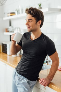 Young man holding cup of coffee and smiling away near worktop in kitchen stock vector