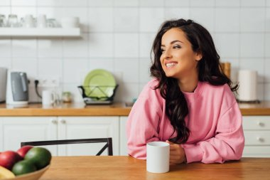 Selective focus of beautiful brunette woman smiling and holding cup of coffee at table in kitchen stock vector