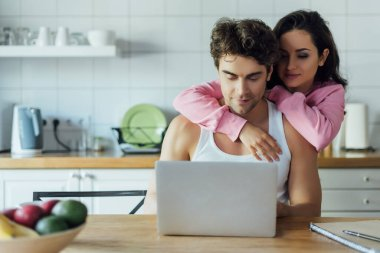 Selective focus of woman embracing boyfriend using laptop in kitchen stock vector