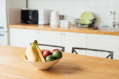 Selective focus of ripe fruits on wooden table in kitchen