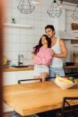 Szelektív fókusz jóképű férfi ölelés gyönyörű barátnő a konyhában
