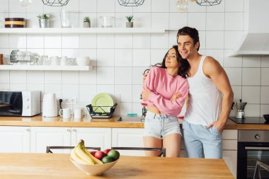 Selective focus of smiling man hugging beautiful woman near worktop in kitchen stock vector