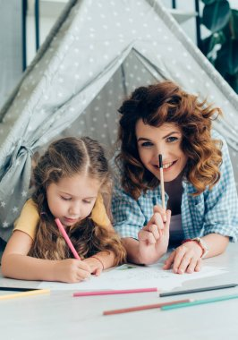 Happy nanny with felt pen smiling at camera while lying in toy wigwam near child drawing with pencil stock vector