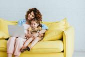 usměvavá chůva a dítě sedí na pohovce a používají notebook společně