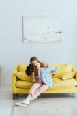 mladá chůva piggybacking šťastný dítě zatímco sedí na žluté pohovce