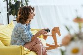 KYIV, UKRAINE - JUNE 19, 2020: selective focus of cheerful woman playing video game with joystick