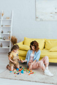 young nanny giving block to cute child while playing on floor in living room
