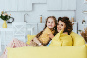veselá chůva a dítě s úsměvem na kameru při objímání na pohovce v kuchyni