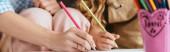 ořezaný pohled na chůvu a dětskou kresbu s tužkami k sobě, vodorovný obraz
