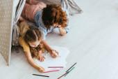 vysoký úhel pohledu na chůva a dítě kreslení při ležení v hračky wigwam
