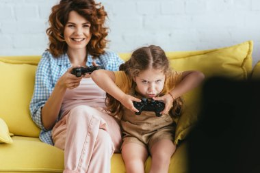 KYIV, UKRAINE - JUNE 19, 2020: selective focus of smiling babysitter and concentrated child playing video game with joysticks stock vector