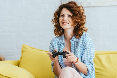 KYIV, UKRAINE - JUNE 19, 2020: smiling young woman sitting on sofa and playing video game with gamepad stock vector
