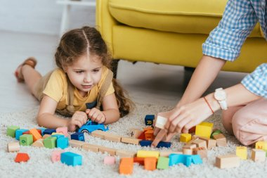 Partial view of babysitter and kid playing with multicolored blocks of floor stock vector