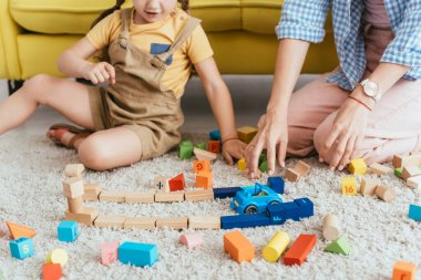 Partial view of child and nurse playing with multicolored blocks and toy car on floor stock vector