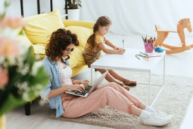 Selective focus of babysitter sitting on floor and working on laptop near kid drawing with pencil stock vector