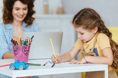Selective focus of cute kid drawing near nanny working on laptop stock vector