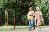 Usmívající se starší žena kráčí v blízkosti manžela na chodníku v parku