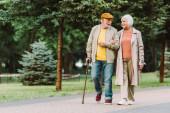 Starší pár usmívá při chůzi po cestě v parku