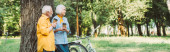 Panoramatický záběr usměvavé starší ženy držící jednorázové pohár vedle manžela a kola v parku