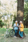 Starší pár usmívá jeden na druhého, zatímco drží papírové poháry v blízkosti stromu a kola v parku