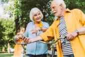 Szelektív fókusz boldog férfi gazdaság okostelefon, míg a feleség ujjal mutogatott közel kerékpárok a parkban