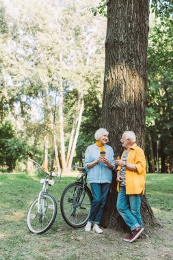 Elderly couple smiling at each other while holding paper cups near tree and bikes in park stock vector