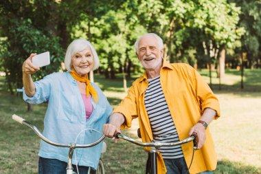 Cheerful senior couple taking selfie near bikes in park stock vector