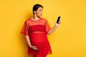 rozrušený těhotné ženy n červená tunika držení smartphone s prázdnou obrazovkou při dotyku břicho na žluté