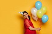 těhotná žena v čepici strany drží pestrobarevné slavnostní balónky na žluté