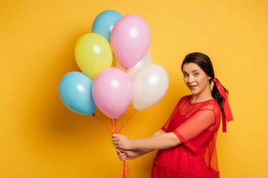 Brunette pregnant woman in red outfit looking at camera while holding colorful festive balloons on yellow stock vector