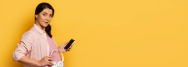 horizontal image of pregnant woman with smartphone holding wireless headphones near belly on yellow