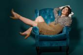 Schwangere in modischer Kleidung posiert im Veloursessel auf dunkelblauem Grund