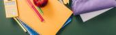 Ansicht von bunten Notizbüchern und Schulmaterialien auf grüner Tafel, horizontales Bild