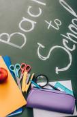 szelektív fókusz vissza az iskolai betűk közelében iskolai levélpapír és friss alma zöld táblán