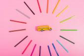 vrchní pohled na školní autobus model zarámovaný barevnými plstěnými pery na růžové