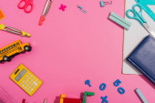 Photo frame of multicolored school stationery on pink with copy space, top view