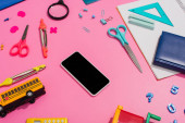 Photo high angle view of smartphone with blank screen near school bus model and stationery on pink