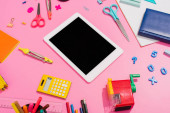 high angle view of digital tablet near notebooks and school supplies on pink