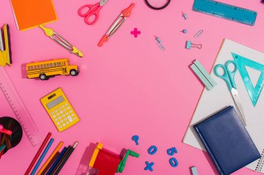 top view of school supplies and school bus model on pink with copy space