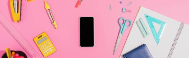 top view of smartphone with blank screen near school stationery on pink, horizontal concept