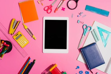 top view of digital tablet with blank screen near school supplies on pink
