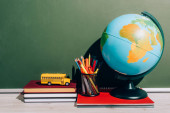 globus a držák pera na notebooku v blízkosti školní autobus model na knihy v blízkosti zelené tabuli